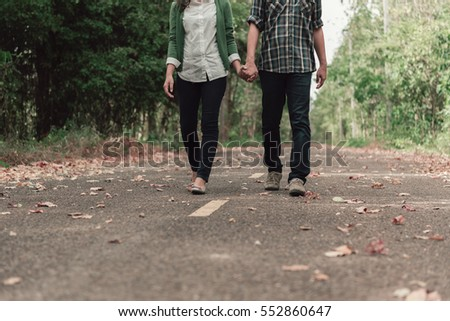 Young couple holding hands and walking through pathway on the street.