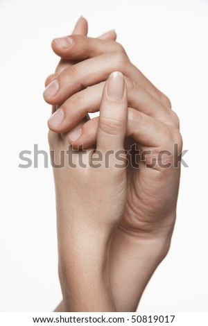 Young couple holding hands, arms raised together, close-up on hands