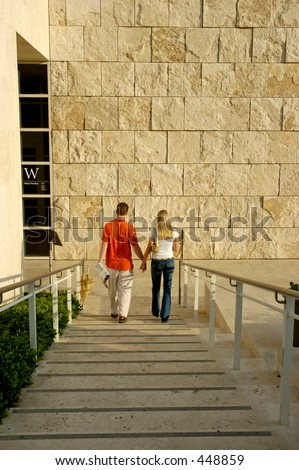 Young couple holding hands going down a set of stairs