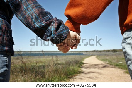 Young couple holding hands in front of long road (happy family relationships contest)