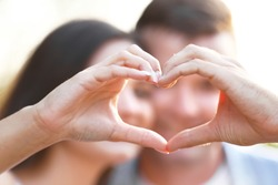 Young couple holding hands in shape of heart