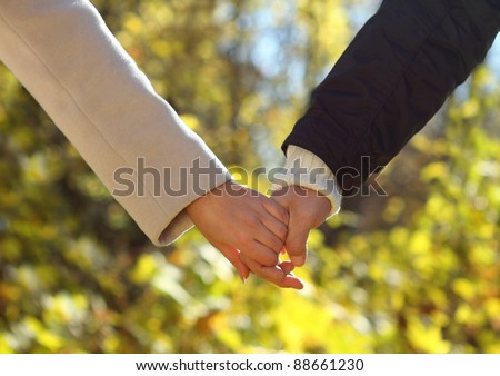 Young couple holding hands in the autumn forest. Close up