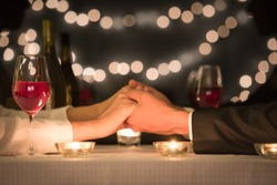 Young couple holding hands on a romantic date night setting.