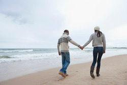 Young couple holding hands walking along winter beach from behind