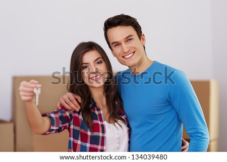 Young couple holding keys in hand to their new home