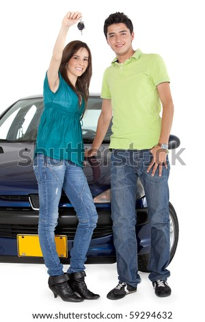 Young couple holding the keys of a car - isolated over a white background
