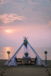 young couple Honeymoon dinner by candle light during sunset on the beach, men and woman having dinner on the beach romantic setting in Thailand during sunset Pattaya