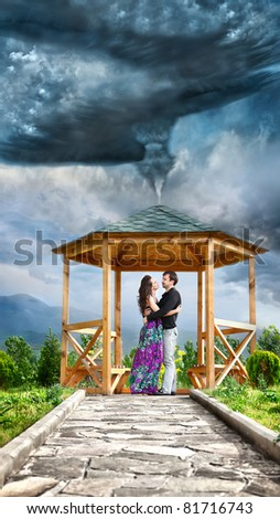Young couple hugging and looking at each other in summer house in the center of tornado