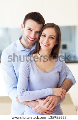 Young couple hugging at home stock photo