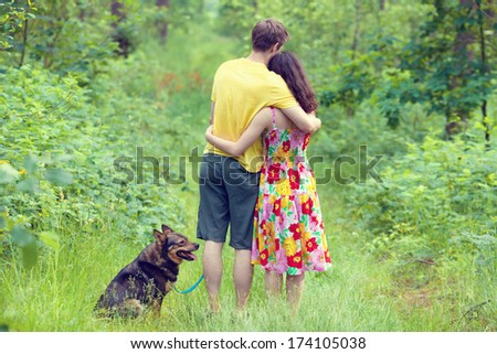 Young couple hugging in the forest. Dog sitting near the couple.