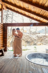 young couple hugging near a vat of water