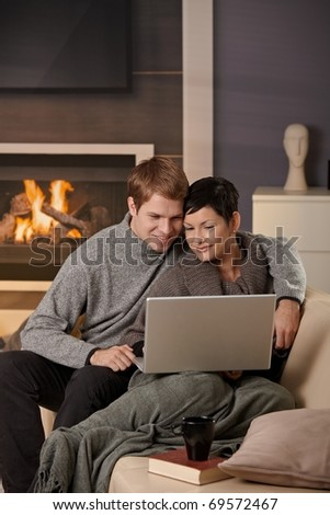 Young couple hugging on sofa at home in winter, using laptop computer, smiling.?
