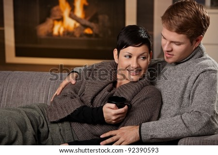 Young couple hugging on sofa in front of fireplace at home, smiling.?