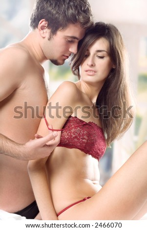 Young couple hugging on the bed in bedroom, in passion