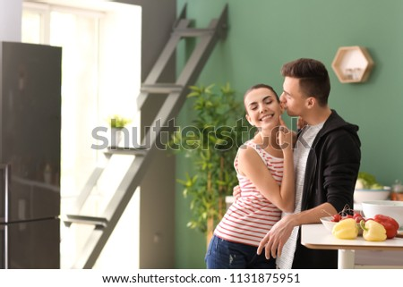 Young couple hugging while cooking together in kitchen #1131875951