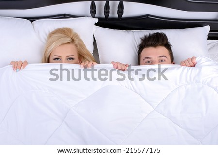 Young couple in a bed, looking out from under blanket