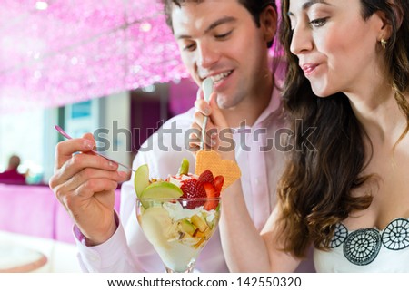 Young Couple in a Cafe or Ice cream parlor, eating an ice cream sundae together #142550320