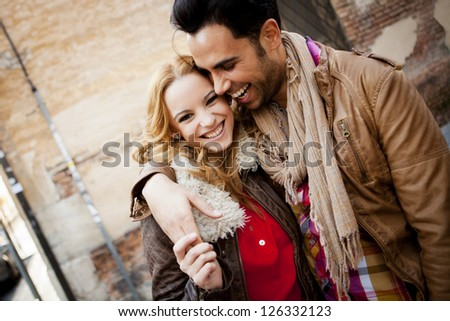 Young couple in a candid shot. They are walking in the street.