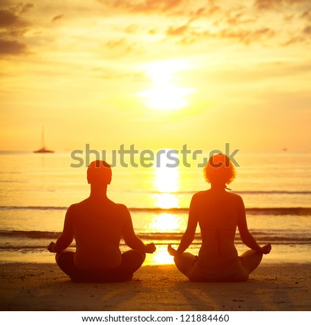 Young couple in a lotus position meditating on the beach at sunset