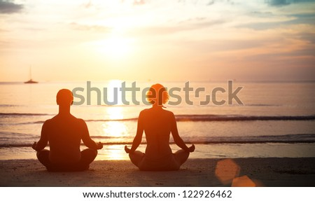 Young couple in a lotus position meditating on the beach at sunset.