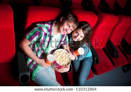 young couple in a movie theater, hugging and happy to have a good time together
