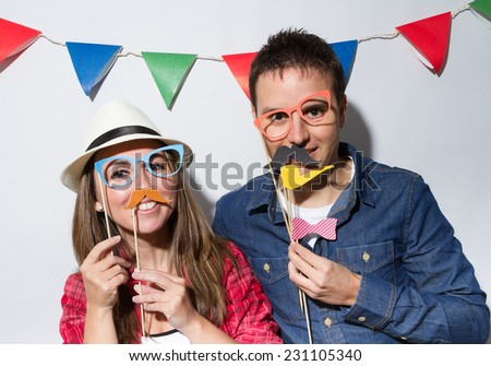 Young couple in a Photo Booth party with garland decoration background
