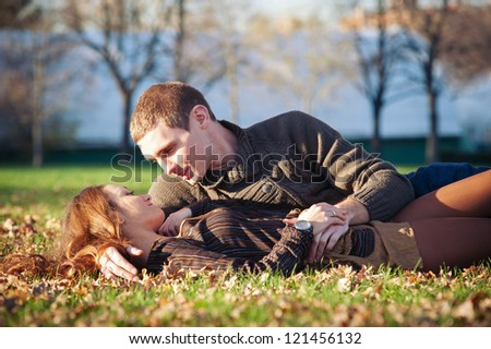 Young couple in a romantic mood lying down outdoors in a park.