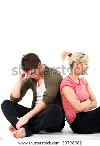 Young couple in an argument sitting on the floor