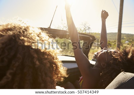 Young couple in an open top car, woman with arms raised #507414349
