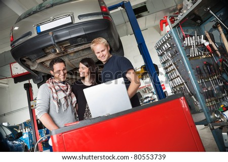 Young couple in auto repair shop standing with mechanic looking at laptop