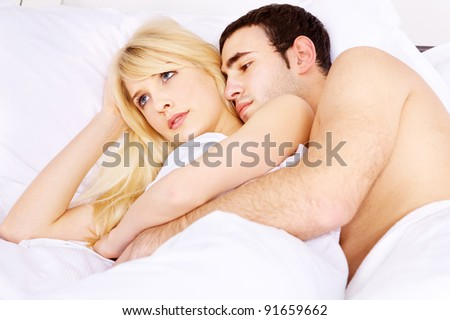 Young couple in bed, he embracing her, focus on woman