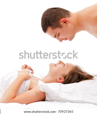 Young couple in bed, man bending over woman