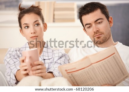 Young couple in bed, man reading newspaper, woman bored, drinking tea.