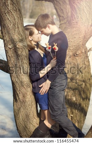 Young couple in blue dress hugging a tree in winter