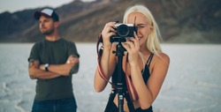 Young couple in casual outfits traveling in Death Valley at evening time and taking pictures with film camera installed on tripod