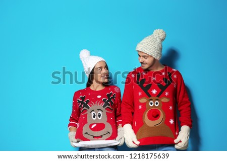 Young couple in Christmas sweaters and knitted hats on color background - Shutterstock ID 1218175639