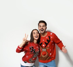 Young couple in Christmas sweaters on white background