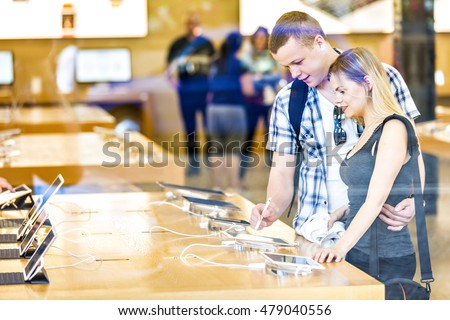 Young couple in consumer electronics retail store browsing at displayed latest tablets, choosing new device. #479040556