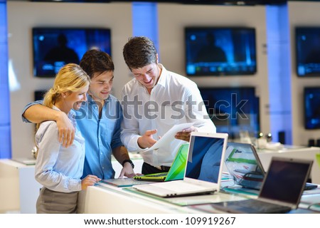 Young couple in consumer electronics store looking at latest laptop, television and photo camera