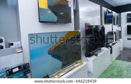 Young couple in consumer electronics store looking at latest laptop, television and photo camera to buy - Shutterstock ID 646218439