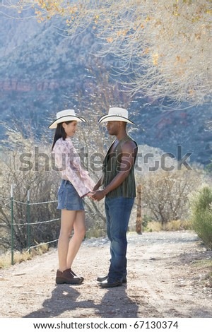 Young couple in cowboy outfit standing on dirt path