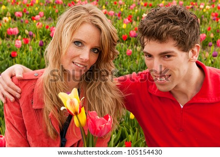 Young couple in Dutch flower fields with colorful tulips