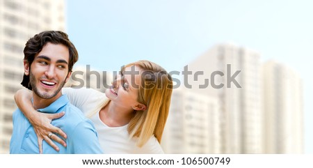 Young couple in front of modern house building. Planning to buy apartment. Mortgage concept
