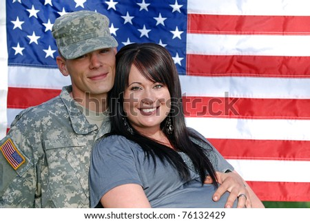 Young couple in front of the United States flag. Young man is in the military.
