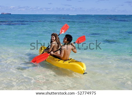 young couple in hawaii paddling a kayak