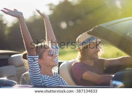 Young couple in his convertible car, happy to drive on a country road, focus on the woman. Shot with flare Сток-фото ©