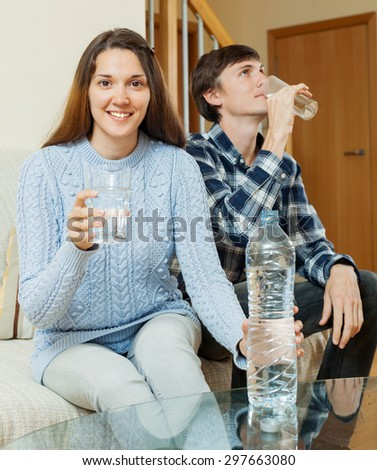 Young couple in home drinking water from plastic bottle