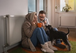 Young couple in jacket and covered with blanket sitting on floor beside radiator with dog and trying to warm up