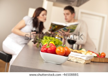 Young couple in kitchen choosing recipe from cookbook drinking red wine