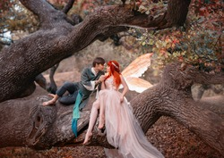Young couple in love. A man and a woman are hugging on huge tree. Themed creative wedding bright fantasy photography. Fairy woman in long pink dress with bright golden wings. A man in an elf costume